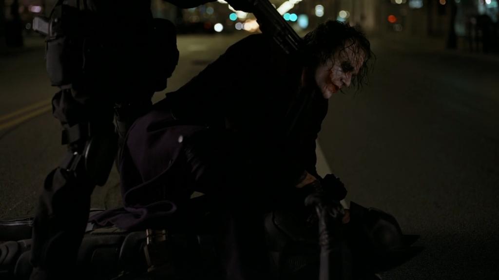 Commissioner Gordon aiming gun at Joker.
