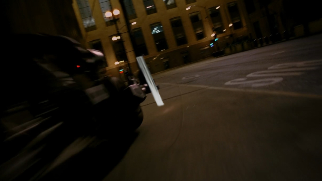 Batman driving into traffic post in Dark Knight